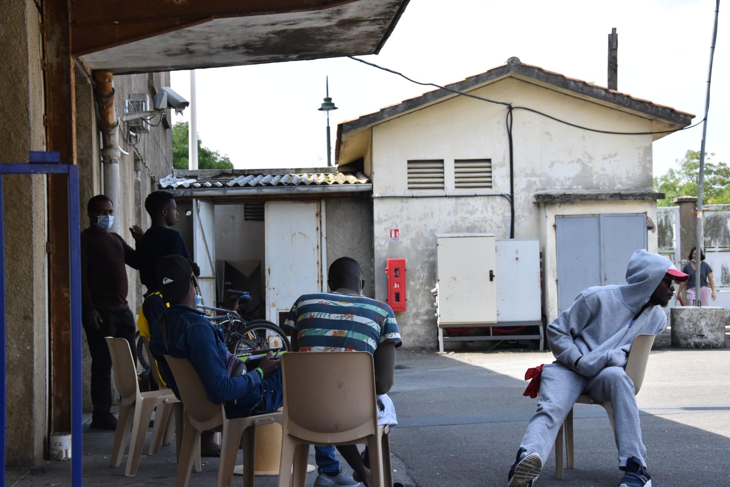Dans la cour du centre d'accueil, les migrants jouent au foot et discutent.